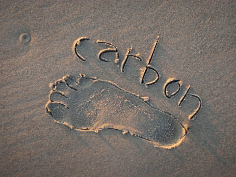 Eco-friendly carbon footprint message handwritten with the outline of a foot on a grainy golden sand beach