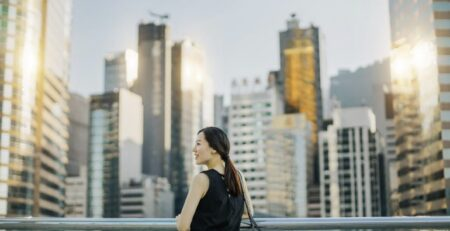 Beautiful young Asian woman enjoying the city view during sunset on urban balcony